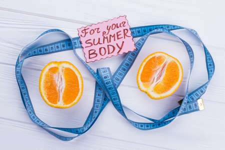 Orange fruit and measuring tape on wooden background. Weight loss and healthy diet. Food for your summer body.
