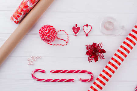 Winter holidays handmade craft background. Rolls of wrapping paper, candy canes, ball of yarn, poinsettia flower, scotch tape. Christmas holiday creativity. Stock Photo