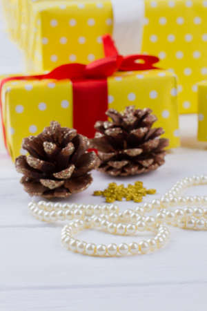 Pine cones, pearl necklace and gift boxes. Christmas holiday decor. Festive holiday atmosphere.