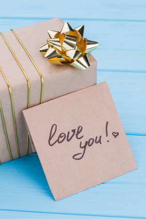 Gift box and i love you note on cardboard. Golden ribbon bow. Blue wood background. Stok Fotoğraf