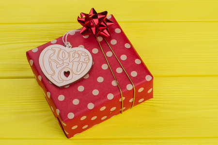Heart shaped wood and red gift boxes. Top view. Yellow wood background.