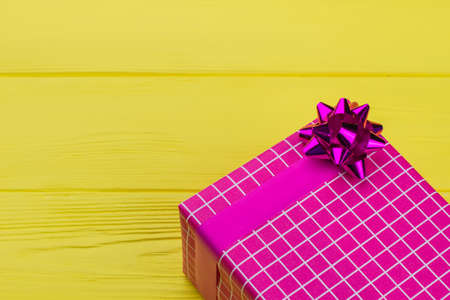 Pink gift box on yellow background. Square present box wrapped in pink patterned paper with bow, copy space. Stock Photo