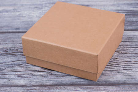 Brown gift box on wooden background. Cardboard box on gray wood. Stock Photo