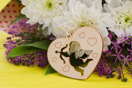 Valentines Day background. Bouquet of fresh flowers and wooden heart shaped ornament. Happy Valentines holiday.