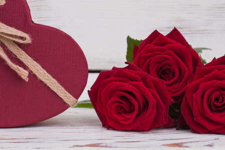 Close up red roses and gift box. Valentine holiday background or Womens Day. Love and romance.