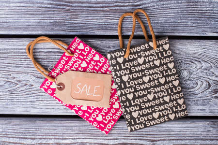 Two shopping bags with Valentine holiday printing. Printed paper gift bags and cardboard tag with inscription sale.