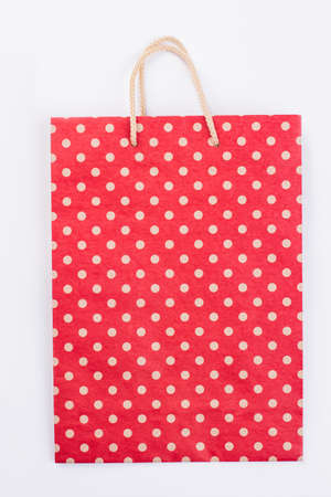 Polka dot paper shopping bag on white background. Red paper gift bag with white dots pattern, vertical image. 版權商用圖片