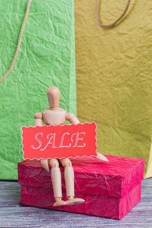 Wooden puppet holding card with inscription sale. Shopping bags, human wooden dummy and message sale. Business, commerce and lifestyle. Stock Photo