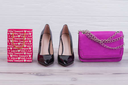 Gift bag, high heels and clutch. Black female shoes, pink clutch and shopping bag. Big fashion sale.