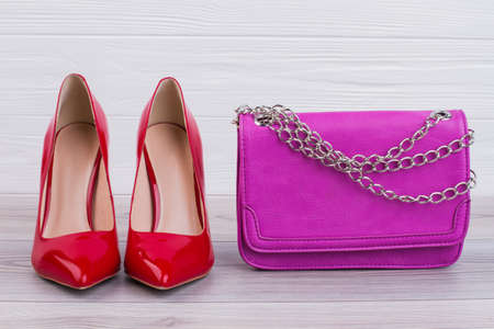 Red high heels and pink bag. Close up luxury female stilettos and chain handbag. Concept of female fashion shopping.