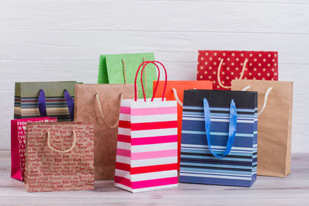 Group of printed paper shopping bags. Assortment of paper carrier bags with printing, horizontal image. Sale, consumerism, advertisement and retail. Фото со стока