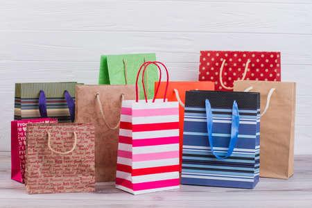Grupo de bolsas de papel impresas. Surtido de bolsas de papel con impresión, imagen horizontal. Venta, consumismo, publicidad y retail. Foto de archivo