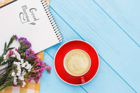 Coffee mug with flowers and notepad with good morning wish. Top view. Blue wooden table background.
