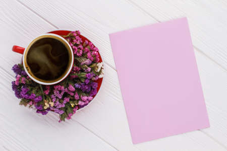 Coffee mug with statice flowers and blank purple paper. Copyspace, free space for text, top view, flat lay. White wood background.