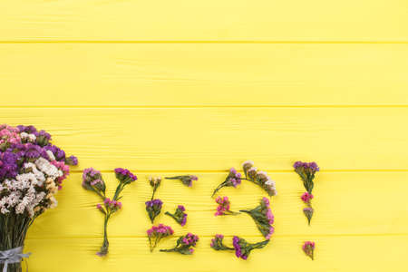 Word yes made of flowers and bouquet on yellow wood. Top view. Copyspace, free space for text. Banque d'images