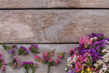 Statice multicolored flowers bouquet and branches. Copyspace, free space for text on wooden table.