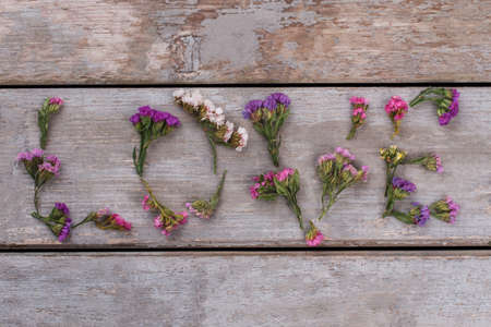 Love word made of statice limonium flowers. Top view. Old vintage wooden desk surface background.