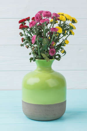 Bouquet of chrysanthemum flowers in green ceramic vase. White wooden background.