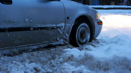 Car stalled in the snow. Close up of car wheel stuck in snow drift. Uncleaned streets with snowdrift after heavy snowstorm.