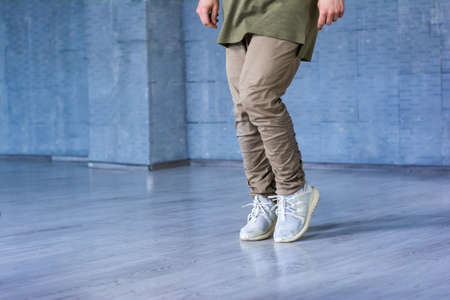 Dancer on grey background, cropped image. Hip-hop dancer wearing grey cotton trousers and sneakers on grey background. Sreet style dancing.