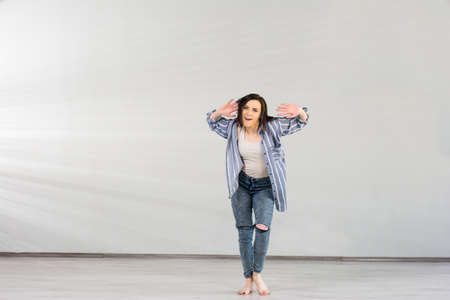 Young woman practicing dance element. Modern style girl posing on studio background performing dance element. Young contemporary dance performer. Stock Photo