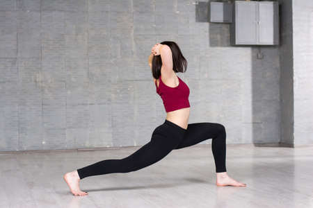 Young woman pacticing dance element. Young female dancer working out in studio. Modern style dancer practicing yoga element.