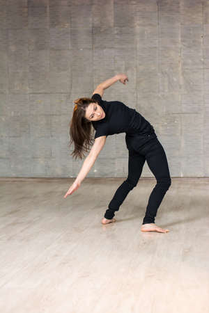 Urban woman dancing in studio. Young woman dancer practicing gymnastic element on studio background. Pretty girl is dancing.