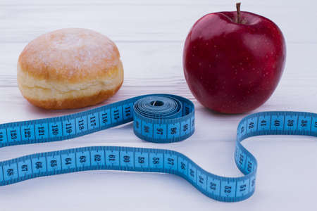 Healthy and unhealthy eating concept. Doughnut, fresh apple and measuring tape. Fatness or perfect body: Make your choice.