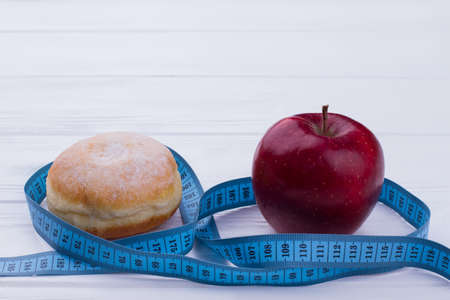 Baked bun, fresh apple and measuring tape. Healthy and unhelathy eating. Slimming and diet concept.