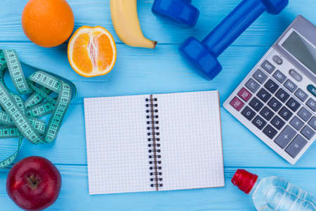 Fruits, fitness equipment, calculator and notepad. Balanced diet, sport and slimming. Tips to boost your weight loss.
