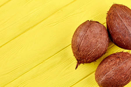 Three brown coconuts and copy space. Close up tropical coconuts fruits on colorful wooden background with text space. Exotic and healthy food. 스톡 콘텐츠