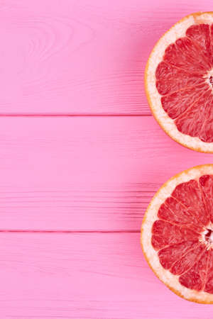 Two halves of grapefruit and copy space. Two slices of ripe grapefruit on pink wooden surface and text space, top view. Stok Fotoğraf