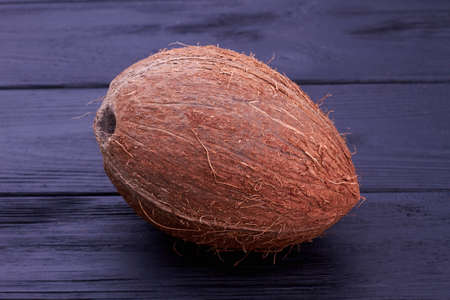 Tropical coconut on dark background. Big whole coconut on black wooden background, horizontal image. Exotic food concept. 스톡 콘텐츠