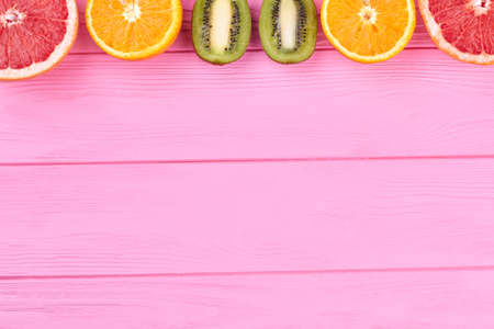Row of fresh citrus fruits and copy space. Ripe tropical fruits on color wooden background with text space.