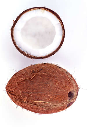 Whole and half coconut, top view. Ripe tropical coconuts on light background. Healthy exotic food.