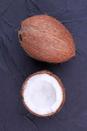 Whole and half of coconut, top view. Whole brown coconut and cracked coconut with yummy pulp on dark background. Health and beauty concept. 스톡 콘텐츠