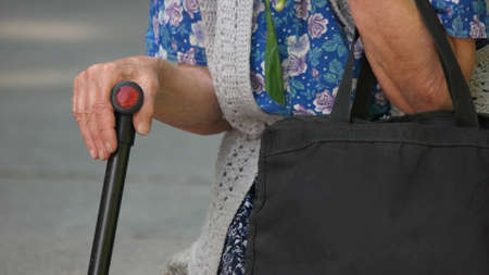 Old woman hand holding a walking cane. Close up hand of elderly woman using walking stick outdoors. Senior people, retirement, healthcare.