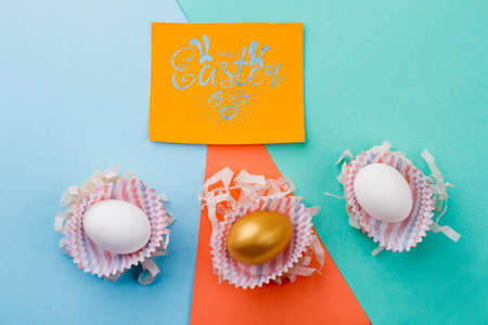 Easter handmade background with eggs. Yellow greeting card and three Easter eggs on colorful paper background. How to make Easter decorations.