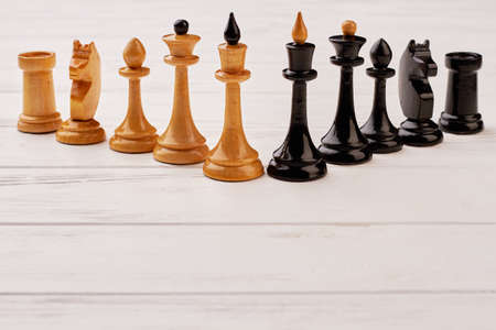 A group of brown and black chess pieces. Collection of wooden chess figures standing on white background. Abstract chess background.
