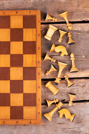 Chess board and chess pieces, top view. White chess figures lying near chess board on rustic wooden boards.