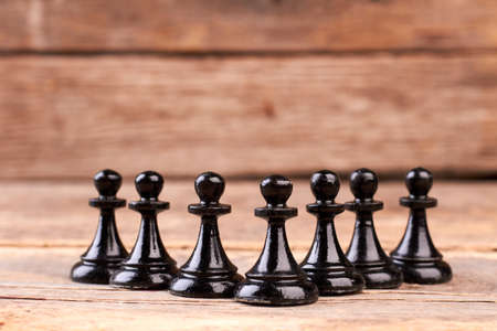 Black chess pawns on rustic background. Group of chess figures on old wood. The rules of classical chess. Imagens