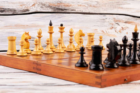 Set of black and white chess pieces. Chess board with chess figures. Concept of competition. Imagens