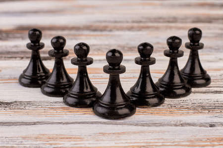 Composition of black chess pawns. Set of black chess pieces on light wooden background. Playing chess for intellectual development.