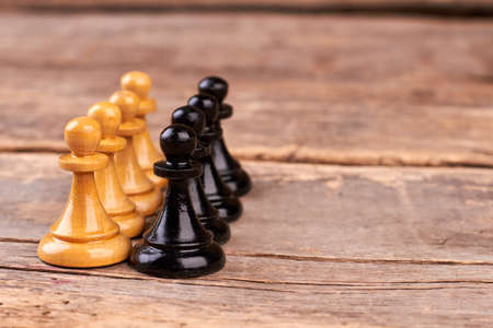 Black and white chess pawns. Set of chess pieces on rustic wooden boards with copy space. Banco de Imagens - 118562970