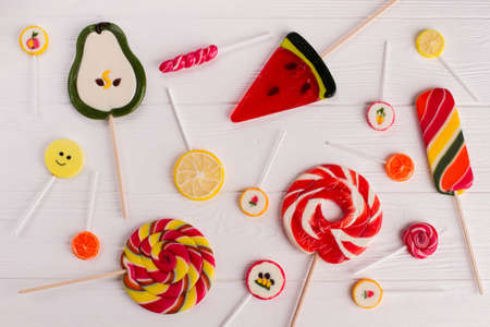 Composition with tasty colorful candies on wooden background. Mixed colorful lollipops on white wood. Stock Photo