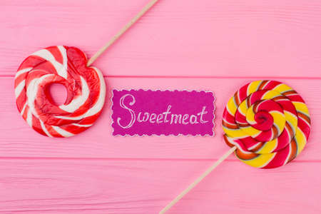 Pink background with colorful lollipops. Round spiral lollipops on sticks and paper card. Color background with sweets.