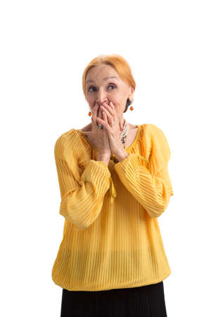 Senior woman covering mouth. Surprised lady on white background. Stock Photo