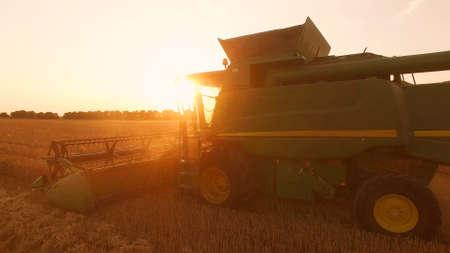 Combine harvester at sunrise. Modern farming methods.