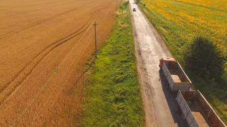 Truck near field. Nature and asphalt road. Basics of commercial farming. Stok Fotoğraf