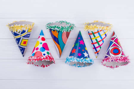 Flat lay colorful party cone hats. Various paper party caps on white wooden background. Imagens